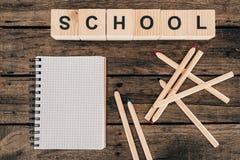 Draufsicht der Zusammensetzung der bunten Bleistifte mit leerer Notizbuch- und Wortschule Stockfoto