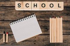 Draufsicht der Zusammensetzung der bunten Bleistifte mit leerer Notizbuch- und Wortschule Lizenzfreie Stockfotos