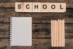 Draufsicht der Zusammensetzung der bunten Bleistifte mit leerer Notizbuch- und Wortschule Lizenzfreie Stockbilder