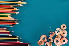 Draufsicht der Zusammensetzung der bunten Bleistifte und der Ausschnitte Lizenzfreie Stockfotos