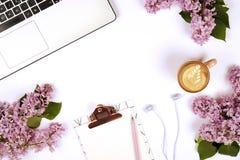 Draufsicht des Arbeitnehmerindesktops mit Laptop, Blumen und verschiedenen Büroartikeleinzelteilen Weiblicher kreativer Designarb stockfotos