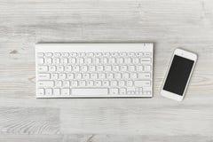 Draufsicht des Arbeitsplatzes mit Tastatur und Smartphone auf Holztisch Lizenzfreies Stockfoto