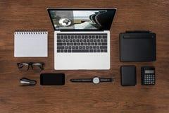 Draufsicht des Arbeitsplatzes mit vereinbarter leerer Lehrbuch Smartphonearmbanduhr und -laptop mit Anmeldung stockbild
