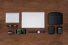 Draufsicht des Arbeitsplatzes mit vereinbarter leerer Lehrbuchlaptop Armbanduhr und Smartphone mit Anmeldung stockbilder