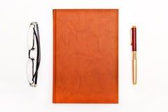 Draufsicht des Arbeitsplatzkonzeptes Tagebuch, Gläser und Stift lokalisiert Lizenzfreie Stockbilder