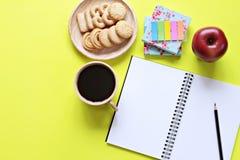 Draufsicht des Arbeitsschreibtisches mit leerem Notizbuch mit Bleistift, Plätzchen, Apfel, Kaffeetasse und buntem Notizblock auf  Lizenzfreies Stockbild
