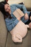 Draufsicht des asiatischen Holdingbuches und -c$schlafens der jungen Frau auf Schlafcouch Mädchen halten im Wohnzimmer ein Schläf lizenzfreies stockbild