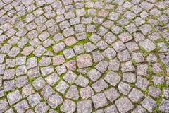 Draufsicht des Bürgersteigs, radial gepflastert mit kleinen quadratischen Granitsteinen Lizenzfreie Stockfotos