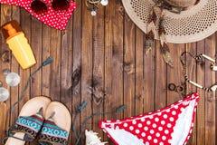 Draufsicht des Badeanzugs, des Hutes, der Sonnenbrille und der Flipflops auf hölzerner Tischplatte Stockbild