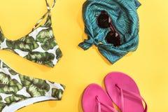 Draufsicht des Badeanzugs, des Schals, der Sonnenbrille und der Flipflops Lizenzfreies Stockfoto