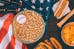 Draufsicht des Baseballballs auf Platte mit Erdnüssen, Baseballschläger, Handschuh, Hotdog und Bierflaschen lizenzfreies stockbild