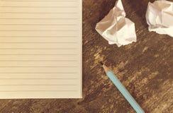 Draufsicht des Bleistiftnotizblockes und des zerknitterten Papiers auf Holztisch Lizenzfreies Stockfoto