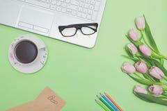 Draufsicht des Designerarbeitsplatzes mit Laptop, rosa Tulpen, Teeschale, Gläsern, Farbbleistiften und Briefpapier auf grünem Hin Lizenzfreies Stockbild