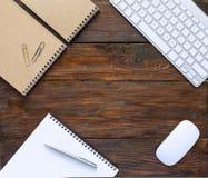 Draufsicht des dunklen hölzernen Schreibtisches mit Tastatur und Briefpapier Lizenzfreies Stockfoto