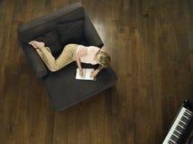 Draufsicht des Frauen-Schreibens im Notizbuch auf Sofa Stockfoto