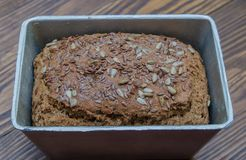 Draufsicht des frisch-gebackenen selbst gemachten Schwarzbrots mit Getreide auf braunem Hintergrund Stockfoto