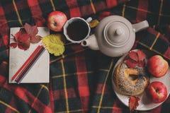 Draufsicht des gemütlichen Herbstmorgens zu Hause Frühstücken Sie mit Topf des Tees und des Bagels mit Äpfeln auf woolen Plaiddec Stockfotografie