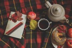 Draufsicht des gemütlichen Herbstmorgens zu Hause Frühstücken Sie mit Topf des Tees und des Bagels mit Äpfeln auf woolen Plaiddec Stockbild
