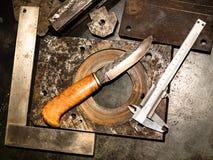 Draufsicht des geschmiedeten Messers und des Tasterzirkels auf Werktisch stockbild
