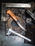 Draufsicht des geschmiedeten Messers und des Tasterzirkels auf Werktisch stockfotografie