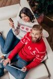 Draufsicht des glücklichen Paars das Eeinkaufen mit Tablette im Weihnachten machend stockfoto