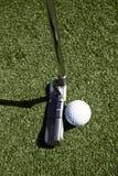 Draufsicht des Golfballs und des Putters hinter Kugel Lizenzfreie Stockfotos