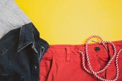 Draufsicht des grauen T-Shirts, der Denimjacke und der roten kurzen Hosen auf gelbem Hintergrund lizenzfreies stockfoto