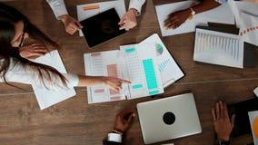 Draufsicht des großen Schreibtisches, hinter dem das Büroteam von kreativen Managern von verschiedenen Nationalitäten macht stock footage