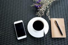 Draufsicht des Handys und des Kaffees mit Blumen mit dem Notizbuch Stockbilder