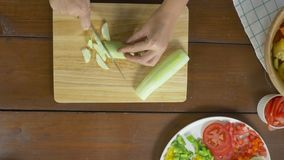 Draufsicht des Hauptherstellungssalats der Frau gesundes Lebensmittel und hacken Gurke auf Schneidebrett in der Küche stock footage