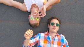 Draufsicht des jungen Mannes liegend mit seinem Freund auf Dach und eine Zigarette gebend ihm Hübsche männliche Paarausgabenzeit stock footage