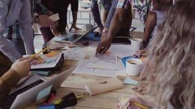 Draufsicht des jungen Teams arbeitend an Architekturprojekt Gruppe Mischrasseleute, die nahe Tabelle und die Diskussion stehen stock footage