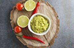 Draufsicht des köstlichen frischen Guacamolen mit Paprikapfeffer, Kalk, Kirschtomaten diente auf hölzernem Behälter stockfotos