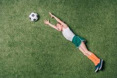 Draufsicht des kleinen Jungen vortäuschend, Fußball auf Gras spielend Stockbild
