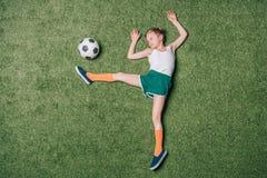 Draufsicht des kleinen Jungen vortäuschend, Fußball auf Gras spielend Lizenzfreie Stockfotografie