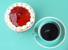 Draufsicht des kleinen Kuchens und des Kaffees über blauen Hintergrund Stockbilder