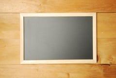 Draufsicht des Kreidebrettes mit hölzernem Hintergrund Stockfotografie