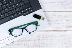 Draufsicht des Laptops, caculator, Gläser und USB-Blitz fahren auf Th Lizenzfreie Stockbilder