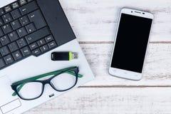 Draufsicht des Laptops, Gläser, Smartphone und USB-Blitz fahren auf t Stockbilder