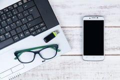 Draufsicht des Laptops, Gläser, Smartphone und USB-Blitz fahren auf t Stockbild