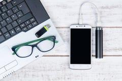 Draufsicht des Laptops, Gläser, Smartphone und USB-Blitz fahren auf t Stockfotografie