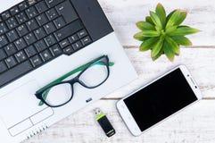 Draufsicht des Laptops, Smartphone, Gläser und USB-Blitz fahren auf t Stockbilder