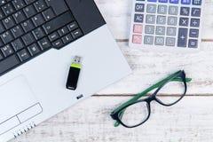 Draufsicht des Laptops, Taschenrechner, Gläser und USB-Blitz fahren auf t Stockfotografie