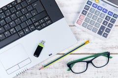 Draufsicht des Laptops, Taschenrechner, Gläser und USB-Blitz fahren auf t Lizenzfreie Stockfotografie