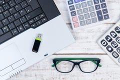 Draufsicht des Laptops, Taschenrechner, Gläser und USB-Blitz fahren auf t Stockfotos