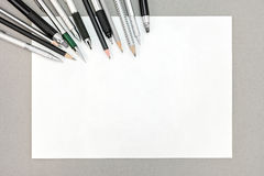 Draufsicht des leeren Papierblattes und der Bleistifte auf grauem Hintergrund Lizenzfreie Stockbilder