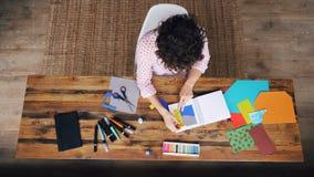 Draufsicht des lockigen Mädchens Design vom Spritzenpapier, das Zahlen im Notizbuch schaffend dann haftet sie unter Verwendung an stock video footage