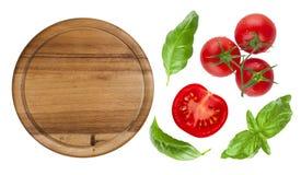 Draufsicht des lokalisierten Schneidebretts mit Tomate und Basilikum Lizenzfreie Stockfotografie