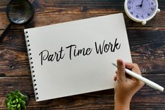 Draufsicht des Lupen-, Betriebs-, Uhr- und Handbehälters, der Teilzeitarbeit auf Notizbuch auf hölzernem Hintergrund schreibt lizenzfreies stockfoto