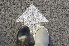 Draufsicht des Mannes die Schwarzweiss-Schuhe tragend, die eine Weise markiert mit weißen Pfeilen wählen Wählt das rechte Wegkonz stockbilder